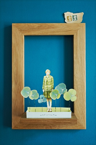 Paper collage in simple oak picture frame on blue wall