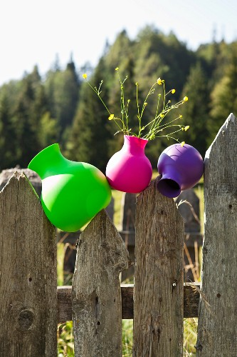 Plastic vases in neon colours on weathered wooden fence