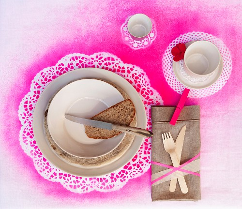 Place setting with slice of bread, cup and saucer on place mat sprayed hot pink through doily stencils
