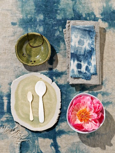 View down onto white spoons and hand-crafted board next to flower in bowl on batik tablecloth