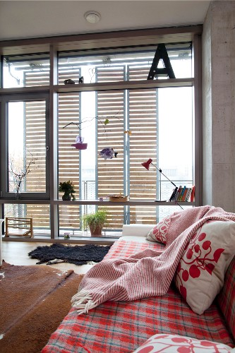 Comfortable sofa with red and white blanket, matching scatter cushions and cowhide rug in front of glass wall with ornaments; wooden, slatted sliding elements on balcony
