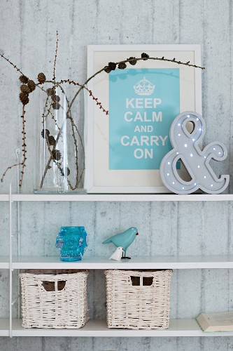 Framed motto, ornaments and white-painted wicker baskets on floating shelves on exposed concrete wall