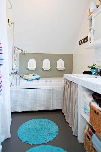 Bathtub with Oriental-style candle arrangement on wall; masonry washstand with baskets on open-fronted shelves to one side