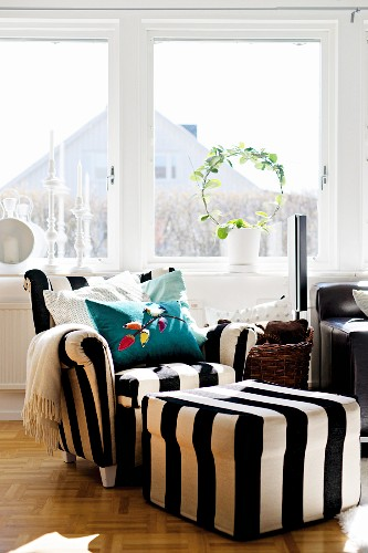 Armchair and pouffe in wide, black and white stripes in front of living room window