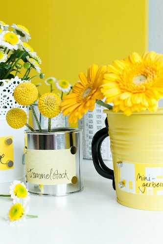 Labelled tin cans used as vases
