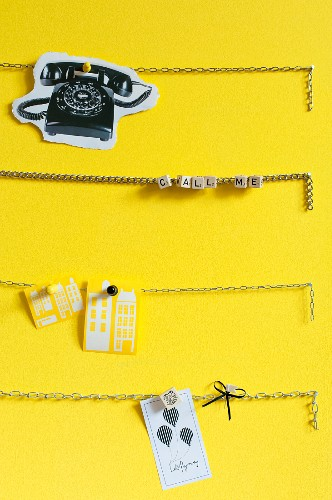 Chains used as pinboard on yellow wall