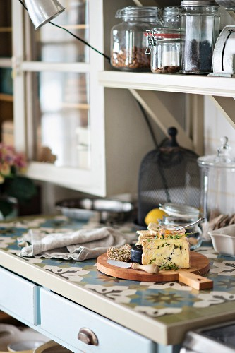 Detail of kitchen counter, cheese on wooden board, storage jars on bracket shelves
