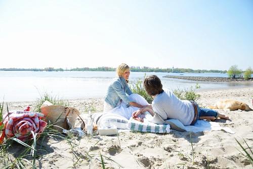 Couple and dog enjoying beach picnic