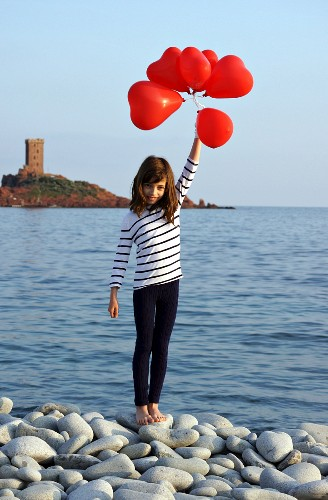 Little girl holding red, heart-shaped balloons on pebbly beach