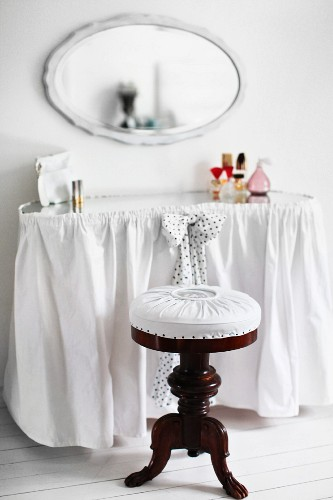 Antique piano stool with white seat cushion at curved dressing table with white curtain