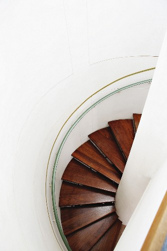 View down spiral staircase with wooden treads in circular stairwell