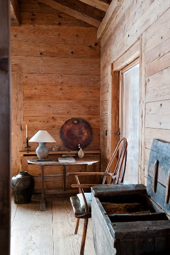 Open wooden trunk next to chair and table lamp on simple table in background in cabin living room