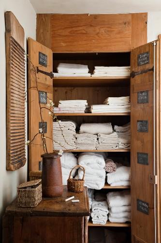 Open, rustic, wooden linen closet built into niche