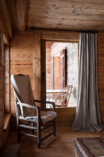 Blanket on rustic armchair next to French window in corner of wooden cabin
