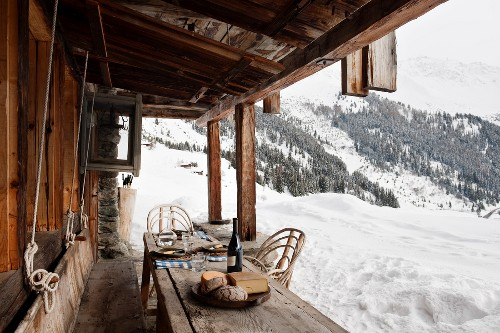 Bread and cheese on rustic wooden table outside cabin with view of winter mountain landscape