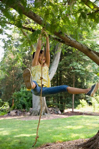 A girl swinging on a rope swing