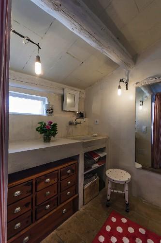 Chest of drawers below masonry washstand in bathroom