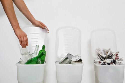 A hand putting a glass jar in a recycling bin