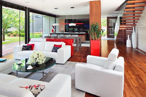 White leather sofa set and coffee table with black stone top in lounge area of open-plan interior with wooden floor and staircase