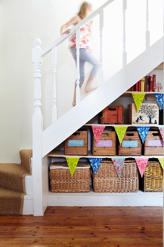 Storage shelves with wooden crates and baskets under white staircase