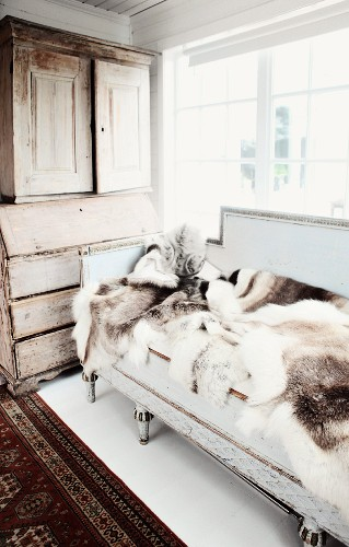 Animal-skin rugs on antique bench below window and antique wooden dresser