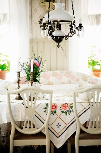 Chairs with white-painted, curved backrests at table below paraffin-lamp-style pendant lamp