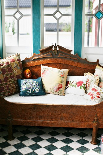 Nostalgic floral scatter cushions on antique wooden bench on chequered floor below Art Nouveau lattice windows