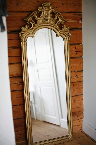 Antique, full.length mirror with gilt, carved frame leaning against wooden wall