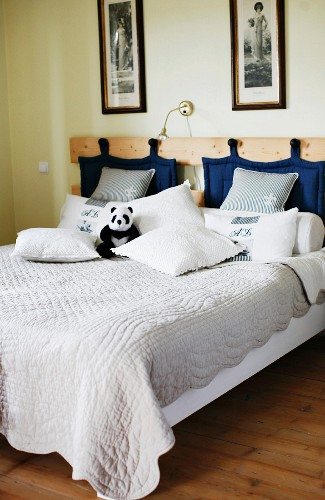 Double bed with quilt and blue quilted pads hanging from hooks on wooden headboard