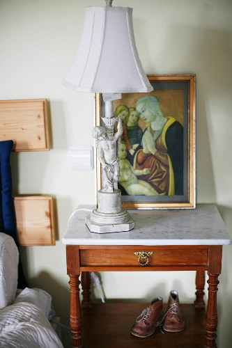 Table lamp with cherub base on wooden bedside table with marble top