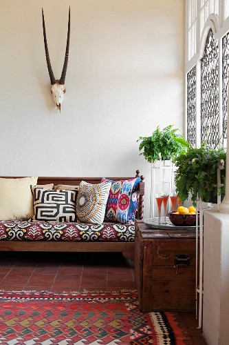 Sofa with ethnic scatter cushions below hunting trophy in living room with Moroccan ambiance