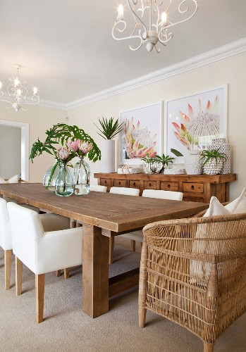 Wooden table, upholstered chairs and wicker armchair in dining room with South-Sea ambiance decorated with king protea