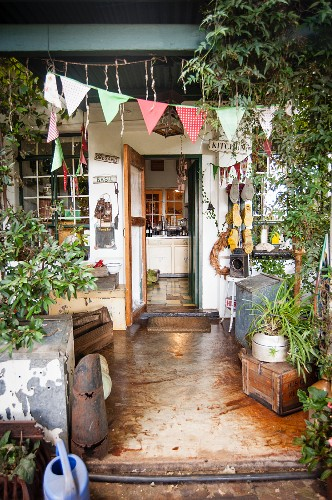 Cluttered vintage terrace decorated with fabric bunting and view into kitchen