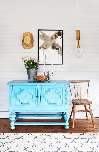 Pale blue, carved dresser and country-house wooden chair below modern artwork on white-painted, wood-clad wall and retro pendant lamp