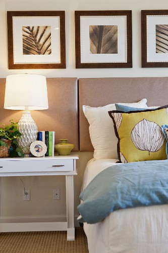 Lit table lamp with picture frames by cropped bed; San Marcos; California; USA
