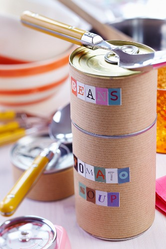 Food cans wrapped in brown paper and labelled with alphabet stickers