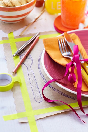 Brown paper place mat stuck down with washi tape and with pen drawing of place setting on set table