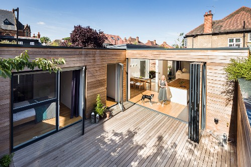 Wooden terrace of contemporary house with wood-clad facade; view of woman and dog in kitchen through open folding doors