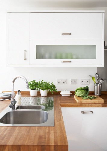 Wall cabinets with lift-up doors above stainless steel sink in wooden work surface in modern fitted kitchen