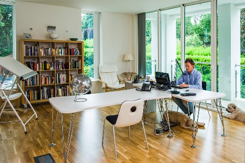 Man working in bright office with designer desks, drawing board and glass sliding doors