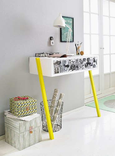 A homemade wall table against a light grey wall made from a white drawer unit decorated with photos and mounted on bright yellow legs with a waste paper basket and storage boxes underneath