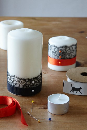 Decorating candles for Halloween using ribbons and trim