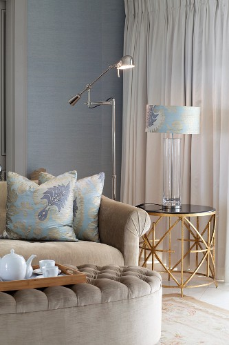 Tea break in elegant living room - tea service on tray on ottoman, sofa with elegant scatter cushions, matching table lamp on side table and stainless steel standard lamp