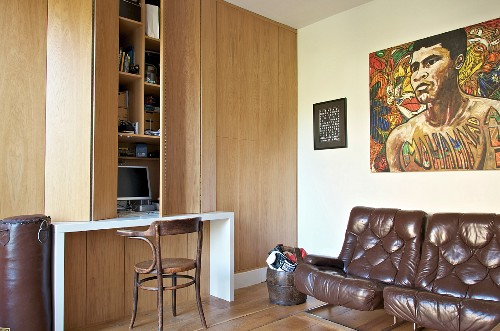 Brown leather easy chairs below artwork, wooden fitted cupboards with integrated desk and Thonet chair