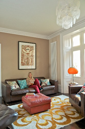 Ottoman with pink leather cover on patterned rug, woman sitting on brown leather sofa in traditional interior