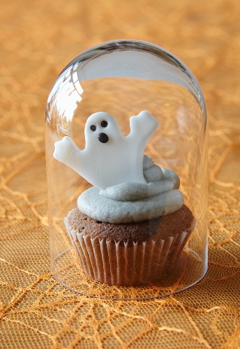 Halloween cupcake with ghost topper under glass cover