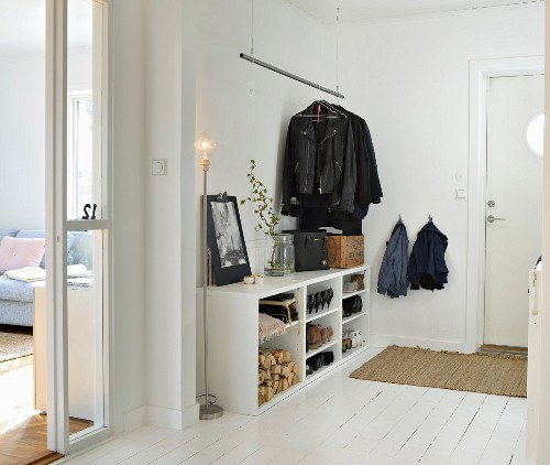 White hallway with open-fronted shoe rack, suspended coat rail and standard lamp in Scandinavian interior