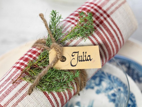 Rolled napkin decorated with name tag and festive sprig of green