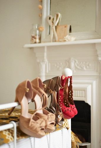 Elegant ladies' shoes hanging on bed frame; open fireplace with white-painted surround in background