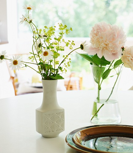 Garden flowers in white retro vase and peony in glass vase on white table